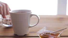 Hand adding sugar to cup of tea and honey on table. Unhealthy eating and drinks concept - hand adding sugar to cup of tea and honey on wooden table stock video