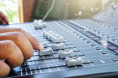 Hand adjusting audio mixer console buttons, faders and sliders. Royalty Free Stock Image