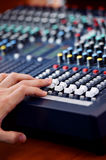 Hand adjusting audio mixer Stock Image