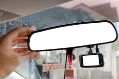 Hand adjusting rear view mirror and camera record video in car. Stock Photos