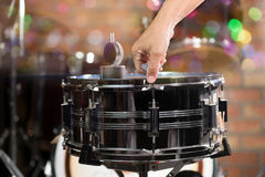 Hand adjusting tension rod of snare drum. Royalty Free Stock Image