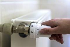 Hand adjusting the valve knob thermostat of heating radiator.  Royalty Free Stock Photo