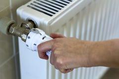 Hand adjusting the valve knob thermostat of heating radiator.  Stock Photography
