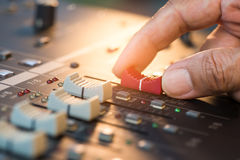 Hand adjusting volume fader of digital audio mixer. Stock Photo