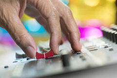 Hand adjusting volume fader of digital audio mixer. Royalty Free Stock Image