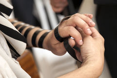 Phylacteries Ceremony Close-Up. The hand of an adult Caucasian man is being wrapped in a leather strap, part of the Jewish phylacteries (Teffilin, Tefilin Stock Photo