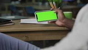 Hand of African American man scrolling web pages on horizontally Smartphone with green screen stock video