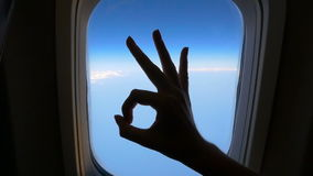 Hand against the sky shows gesture OK. Inside the aircraft, near the window. HD. Hand against the sky shows gesture OK. Inside the aircraft, near the window stock video footage