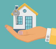 Hand agent with house in palm and key on tube. Offer of purchase house, rental of real estate. Offering, demonstration, handing ho. Hand agent with house in palm Stock Photo