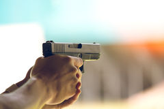 Hand aim pistol in academy shooting range. With flare and vintage color royalty free stock images