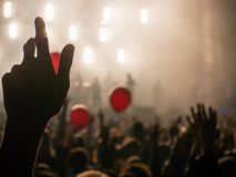 Hand in the air during rock concert silhouetted against bright lights royalty free stock photography