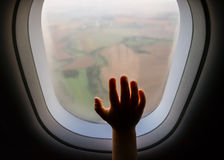 Hand on an airplane window with landscape in the the blurred background Royalty Free Stock Photo