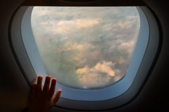 Hand on an airplane window with landscape in the the blurred background Stock Images