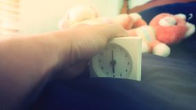 Alarm clock 6 o` clock in the morning on the bed at home. Morning time background concept, soft focusing and vintage color style. Hand on Alarm clock 6 o` clock royalty free stock image