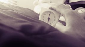 Alarm clock 6 o` clock in the morning on the bed at home. Morning time background concept, soft focusing and vintage color style. Hand on Alarm clock 6 o` clock stock images