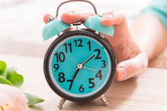 Hand on the alarm clock royalty free stock photo