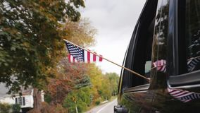 A hand with an American flag looks out of the window of a traveling car. Slow Motion video. A hand with an American flag looks out of the window of a traveling stock footage