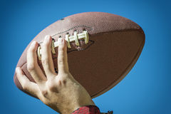 Hand with american football. Closeup of a hand with american football and blue sky in background Stock Photography