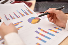 Hand analyzing income graphs and charts Royalty Free Stock Photos