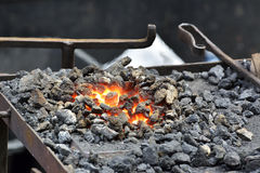 Hand anvil with coal. fire Stock Photography