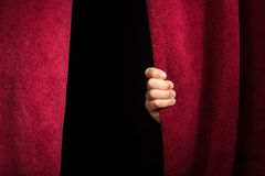 Hand appearing beneath the curtain. Royalty Free Stock Photos