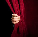 Hand appearing beneath the curtain. Royalty Free Stock Photo