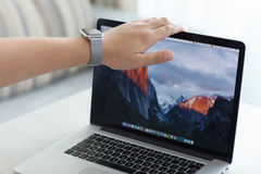 Hand Apple Watch open MacBook Pro with wallpaper macOS Sierra. Alushta, Russia - July 30, 2016: Apple Watch in man hand open MacBook Pro with wallpaper macOS Stock Photography