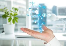 Hand with application blue icons coming up form it. Blurred office background Royalty Free Stock Photo