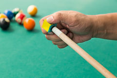 Hand applying chalk on tip of billards pool stick. With table and ball at background Royalty Free Stock Photo