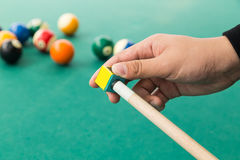 Hand applying chalk on tip of billards pool stick. With table and ball at background Stock Image