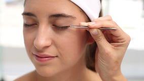 Hand applying eyeshadow to a beautiful woman stock footage