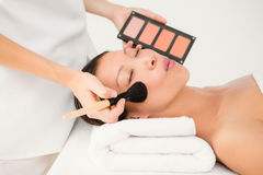 Hand applying makeup to beautiful woman Stock Photo
