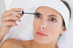 Hand applying mascara to beautiful woman Stock Image