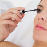 Hand applying mascara to beautiful woman Stock Images