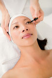 Hand applying mascara to beautiful woman Royalty Free Stock Photos