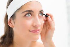 Hand applying mascara to beautiful woman Stock Images