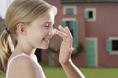 Hand Applying Sunscreen To Girl's Nose Stock Image