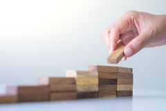 Hand aranging wood block stacking as step stair. Royalty Free Stock Images
