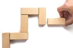Hand aranging wood block stacking as step stair. Stock Image