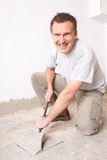 Hand arbeider die oude vloertegels demonteert Stock Foto