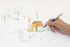 Hand with Architect's plans. The house on top of architecture blueprints Stock Photography
