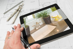 Hand of Architect on Computer Tablet Showing Bathroom Details Ov. Hand of Architect on Computer Tablet Showing Luxury Bathroom Details Over House Plans, Compass Royalty Free Stock Photo