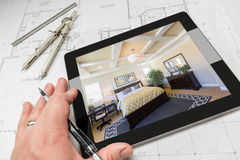 Hand of Architect on Computer Tablet Showing Bedroom Over House. Hand of Architect on Computer Tablet Showing Custom Master Bedroom Over House Plans, Compass and Stock Photo