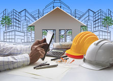 Hand of architect working on computer tablet  with construction. Industry and engineer working tool on top of table against home out line and sketching of Royalty Free Stock Photography