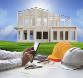 Hand of architect working on computer tablet  and house construc Royalty Free Stock Photos