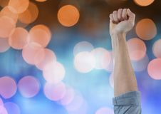 Hand arm celebrating with fist and sparkling light bokeh background stock images