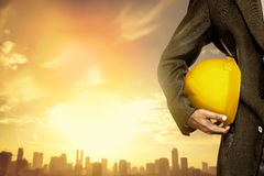 Hand or arm of engineer hold yellow plastic helmet for worker Royalty Free Stock Images