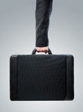 Hand and arm holding brief case Stock Images