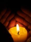 Hand around illuminated candle Stock Photos