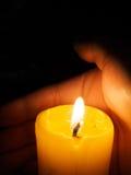 Hand around illuminated candle Stock Photo